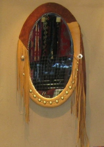 Oval mirror with leather wrapping, brass studs and extended fringe.